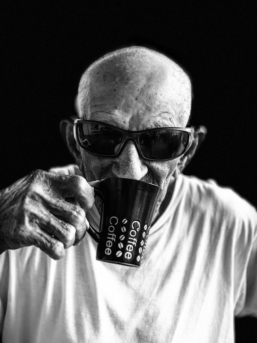 man in white crew neck shirt wearing black sunglasses holding black ceramic mug